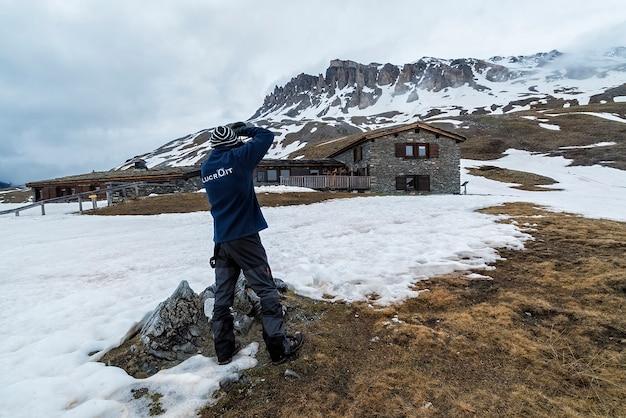 Fotografo che scatta foto di montagne delle alpi vicino a un rifugio