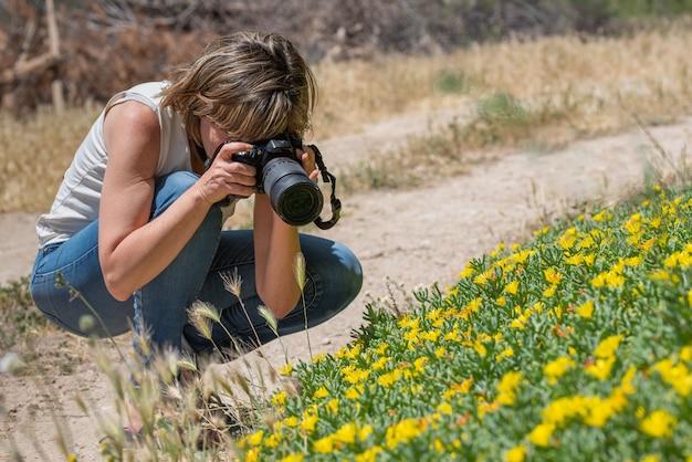Fotografo che cattura scena dei fiori gialli nel campo