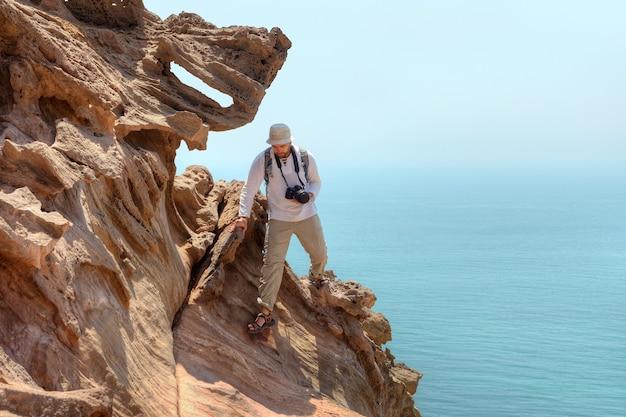 Fotografo viaggiatore si arrampica sulla scogliera sopra il mare, isola di hormuz, hormozgan, iran.