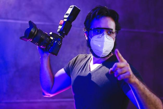Fotografo che indossa la maschera kn95 con una fotocamera professionale dietro le quinte della produzione video, concetto di protezione dal coronavirus