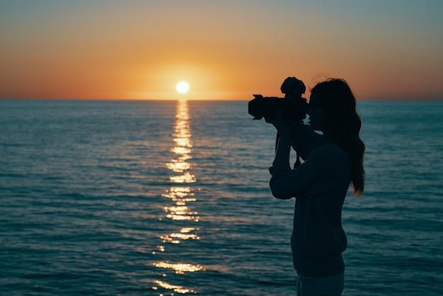 Fotografo con una macchina fotografica al tramonto vicino al mare