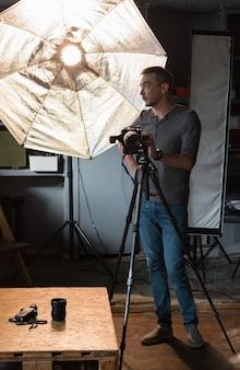 Fotografo con fotocamera su un treppiede sullo sfondo dell'attrezzatura di illuminazione