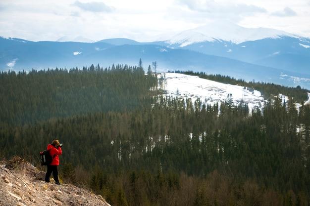 Fotografo con montagne nel cielo nuvoloso e foresta