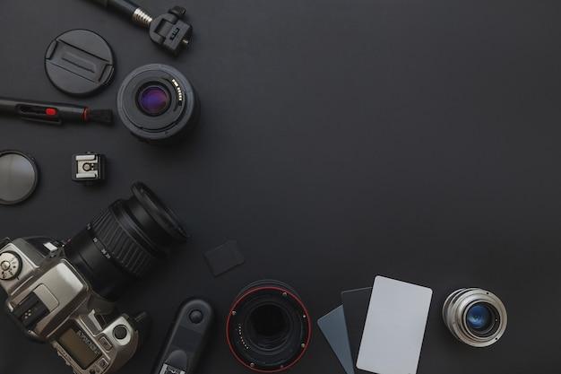 Posto di lavoro del fotografo con sistema di fotocamera dslr e accessorio per fotocamera su sfondo nero scuro