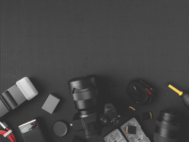 Posto di lavoro del fotografo con la macchina fotografica digitale, taccuino, scheda di memoria, smartphone sulla tavola