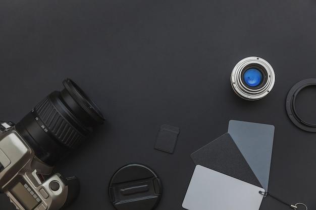 Posto di lavoro del fotografo con sistema di fotocamera dslr, kit di pulizia della fotocamera, obiettivo e accessorio per fotocamera su sfondo nero scuro del tavolo. concetto di fotografia di viaggio per hobby. spazio di copia piatto vista dall'alto