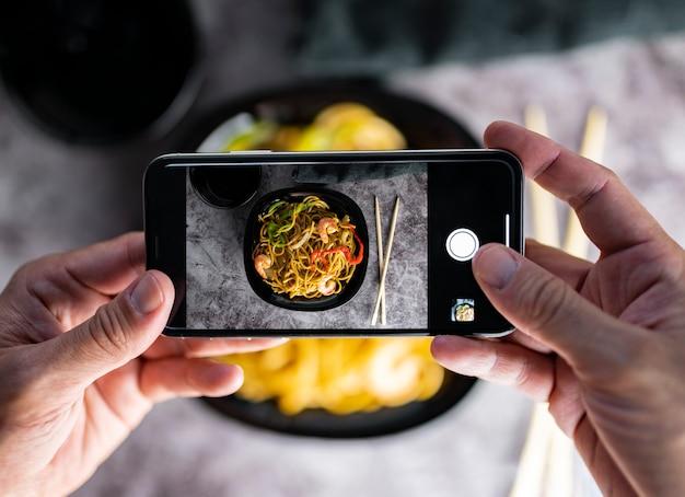 Fotografare il cibo. mani che scattano foto di deliziosi spaghetti di verdure con lo smartphone