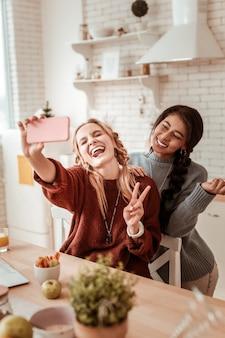 Fotografare per selfie. ragazze che ridono pazze che indossano maglioni caldi oversize mentre si divertono durante il servizio fotografico individuale