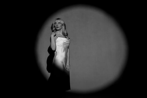 Fotografare con proiettori, bianco e nero, chiaro e scuro, con la figura di una bella ragazza in posa, tonificante alla moda.