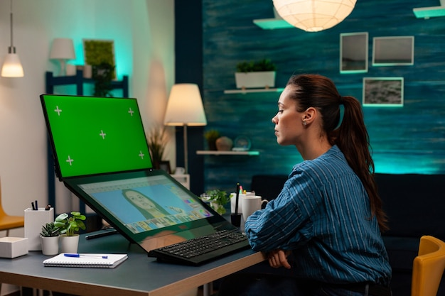 Designer di fotografia che lavora al ritocco di foto con schermo verde sul display. donna professionale che utilizza modello di mockup e chiave cromatica isolata su software grafico in studio di modifica