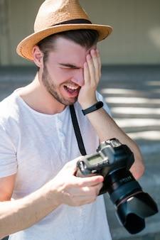 La fotografia fallisce. fotografo professionista ride di qualche brutto scatto. stupidi errori accidentali. concetto di processo di lavoro