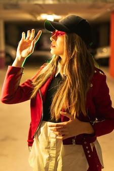 Fotografia con neon rossi e verdi in un parcheggio. giovane donna caucasica abbastanza bionda in un vestito rosso, occhiali da sole e un berretto nero, foto verticale
