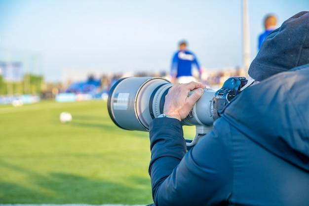 Fotoreporter con teleobiettivo su una partita di calcio