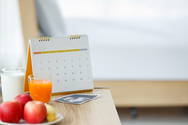 Foto del calendario, un bicchiere di succo d'arancia e latte con un piatto in ceramica bianca di mele e banana e un'immagine di scansione a ultrasuoni su un tavolo di legno. messa a fuoco selettiva su un calendario.