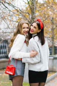 Foto di due ragazze, amiche affascinanti che passeggiano nel parco autunnale, godendosi il tempo