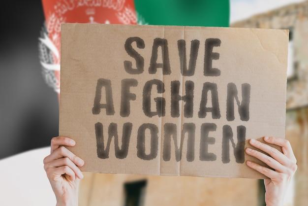 La frase salva le donne afgane su uno striscione in mano da uomo con bandiera afgana sfocata afghanistan