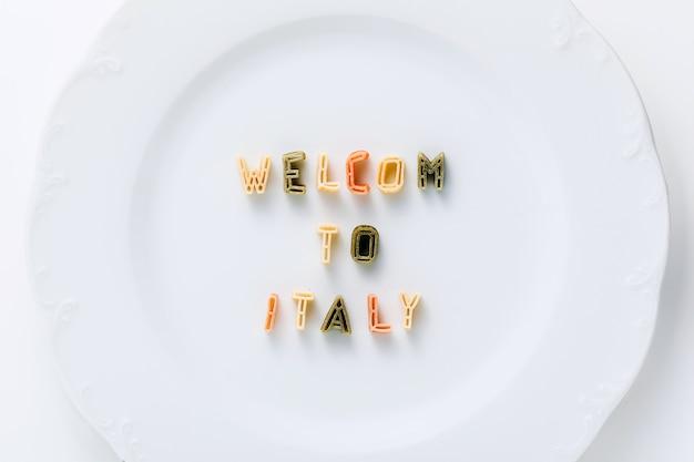 Frase benvenuto in italia da pasta secca multicolore su un piatto bianco.