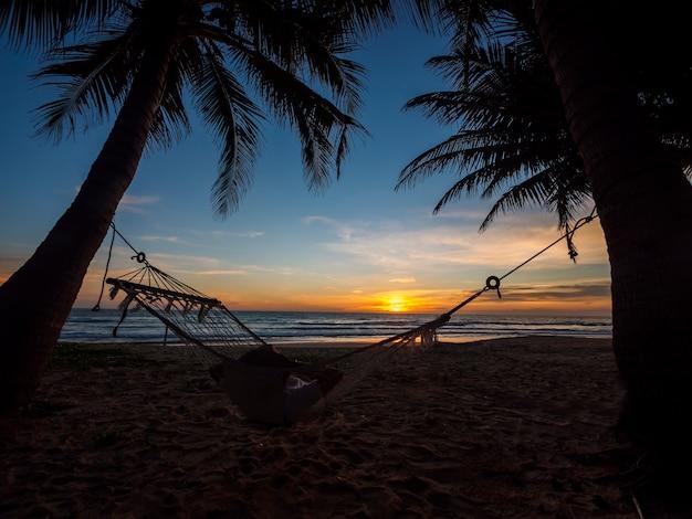 Spiaggia di phuket thailandia. silhouette di giovani donne rilassarsi seduti su amaca e palme sulla spiaggia tropicale al tramonto. amaca su una palma e abbagliamento del tramonto vicino alla sabbia della riva del cielo dell'oceano del mare.