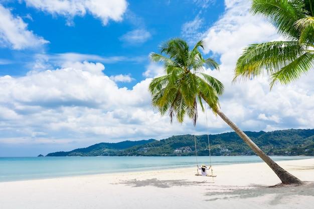 Phuket thailandia paradiso della spiaggia tropicale con altalena da spiaggia con ragazza in camicia bianca le donne si rilassano sull'altalena sotto la palma da cocco in una bellissima spiaggia tropicale di sabbia bianca