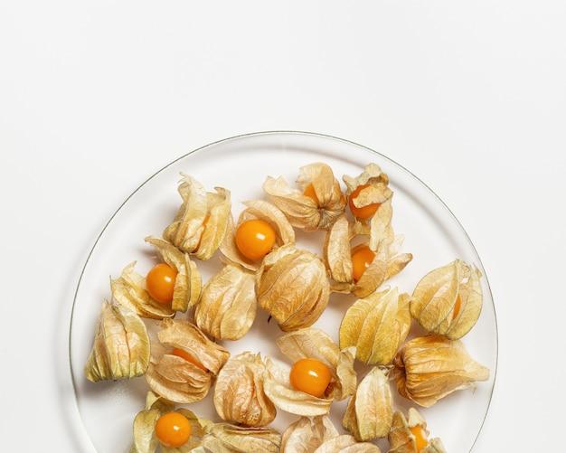 Bacche di physalis o bacche dorate in lastra trasparente su sfondo bianco alimento di frutta physalis