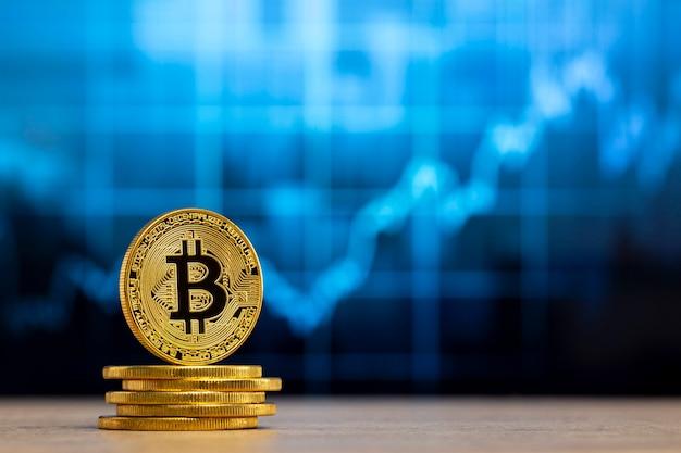 Bitcoin fisico in piedi a un tavolo di legno davanti a un grafico blu