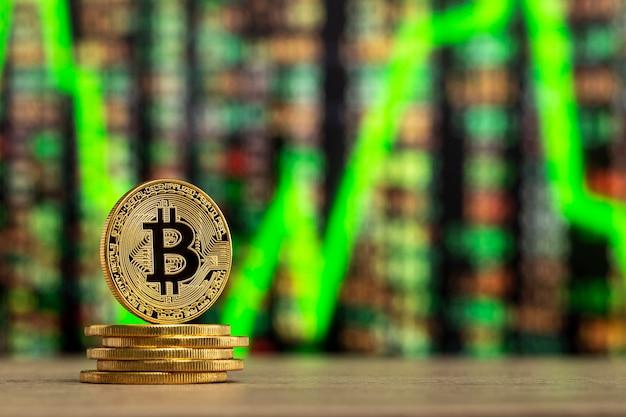 Bitcoin fisico in piedi a un tavolo di legno davanti a un grafico di numeri