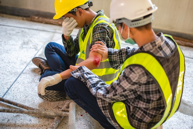 Lesioni fisiche sul lavoro di operaio edile. ferita sanguinante da incidente sul lavoro in una pila di ponteggi in acciaio che cade per urtare il braccio.