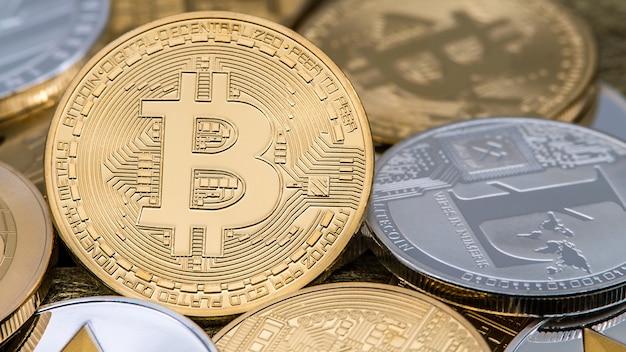 Valuta bitcoin dorata in metallo fisico rispetto ad altre monete. nuovo denaro internet virtuale in tutto il mondo. moneta digitale cyberspazio criptovaluta oro btc. buon investimento futuro pagamento online