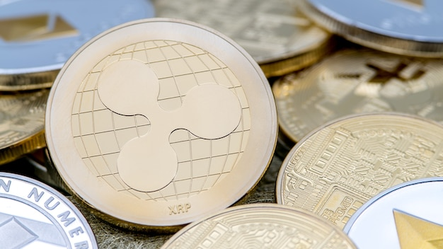 Valuta ripplecoin dorata in metallo fisico rispetto ad altre monete. denaro internet virtuale in tutto il mondo. moneta digitale ripple nel cyberspazio, criptovaluta oro xrp. buon investimento futuro pagamento online