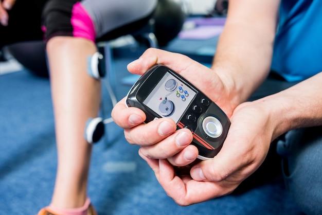 Il fisioterapista installa l'elettrostimolatore sui muscoli delle gambe.