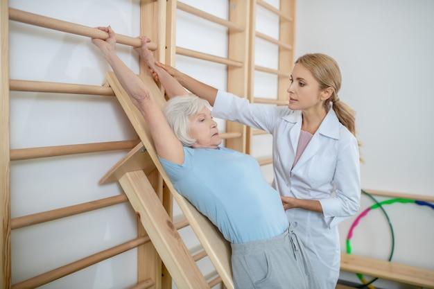 Fisioterapista che istruisce un paziente anziano vicino alla scala a muro