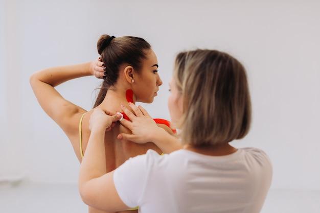 Fisioterapista posizionando il nastro kinesio sulla spalla e sul collo della paziente