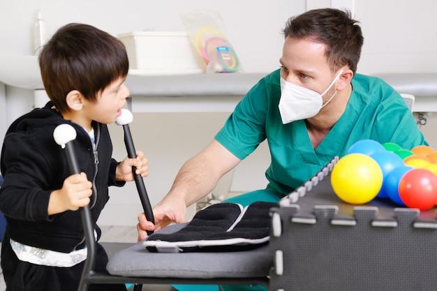 Fisioterapista che gioca con i bambini, con paralisi cerebrale.