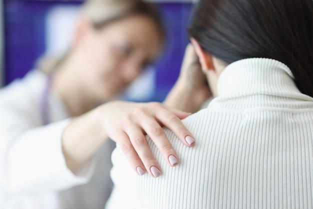 Il medico tiene con simpatia il primo piano della spalla del paziente sconvolto