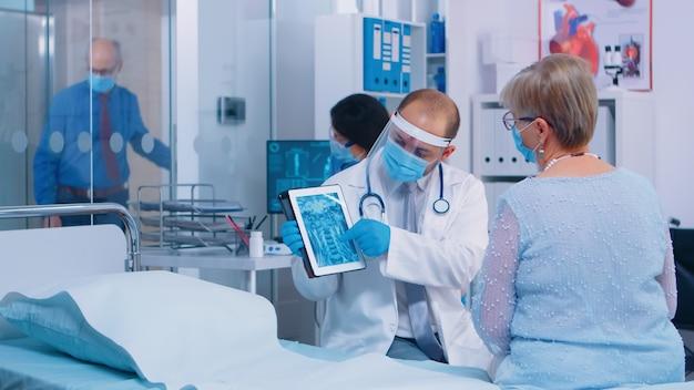 Medico in equipaggiamento protettivo e maschera che mostra la scansione radiologica della donna in pensione su tablet digitale. moderna struttura sanitaria privata, ospedale o clinica durante la crisi globale del coronavirus. infezione medica