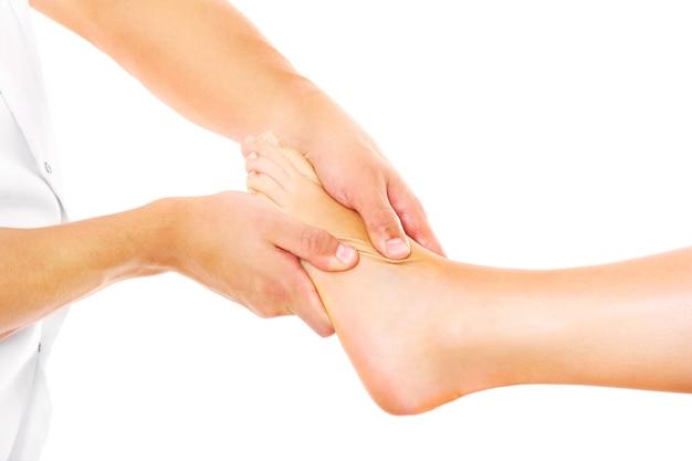 Un fisioterapista che fa un massaggio ai piedi su sfondo bianco