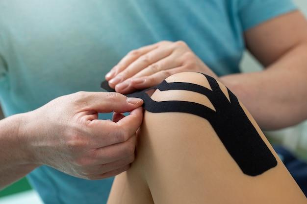 Fisioterapista che applica nastro kinesiologico al ginocchio del paziente