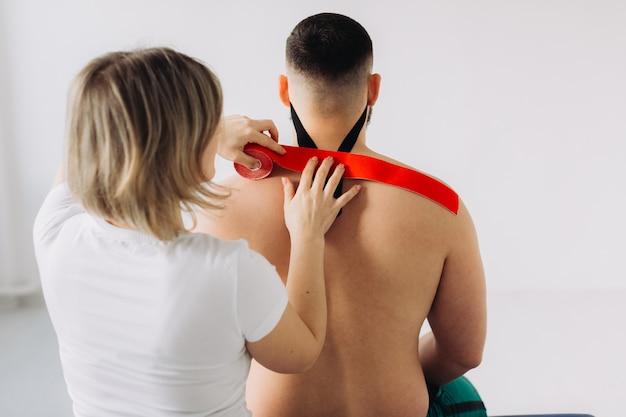 Fisioterapista che applica nastri kinesio rossi e neri ai pazienti nel suo ufficio.