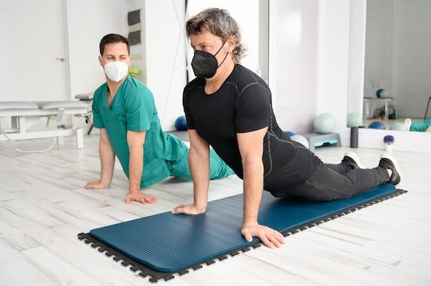 Fisioterapista che assiste l'uomo nell'esecuzione dell'esercizio sulla stuoia.