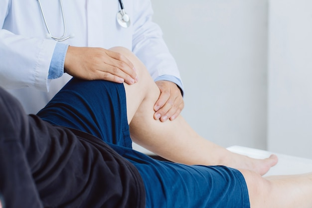 Medico fisioterapista che lavora esaminando il trattamento della gamba ferita del paziente di sesso maschile e dando esercizio di trattamento della gamba del paziente maschio in clinica fisioterapica.