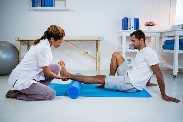 Fisioterapista che fa terapia della gamba ad un uomo che usando il rotolo di schiuma