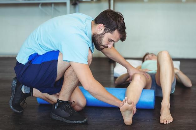 Fisioterapista che fa terapia della gamba ad una donna che usando il rotolo di schiuma