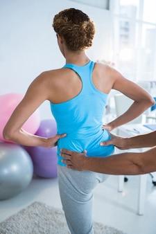 Fisioterapista che esamina la parte posteriore della donna