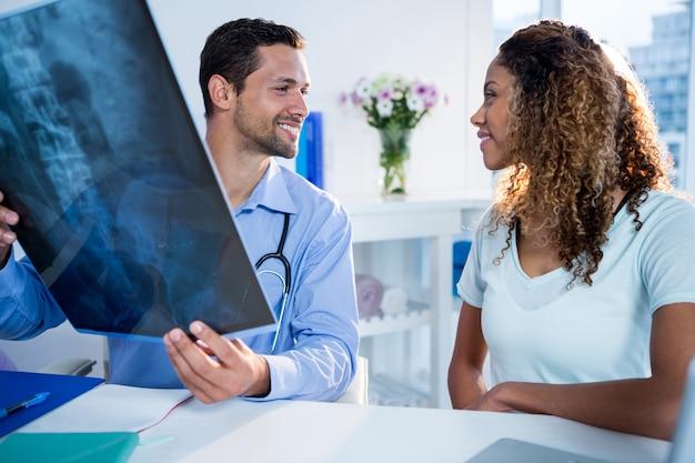 Fisioterapista che spiega raggi x al paziente