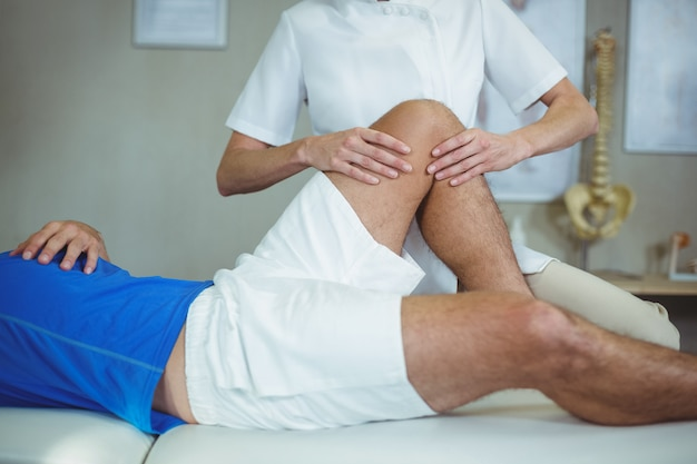 Fisioterapista che dà massaggio ai piedi a un paziente