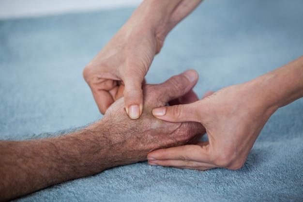 Fisioterapista che dà massaggio della mano al paziente