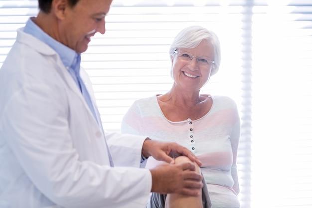 Fisioterapista che dà terapia del ginocchio alla donna senior