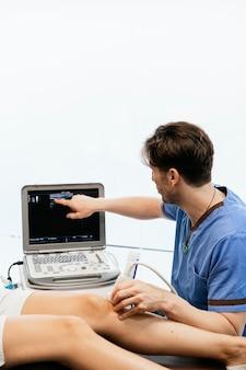 Fisioterapista che dà la terapia del ginocchio a una donna in clinica. concetto di trattamento fisico