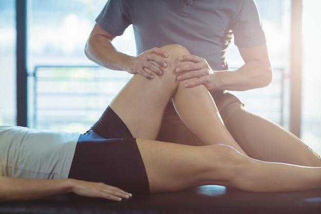 Fisioterapista che dà terapia del ginocchio ad una donna