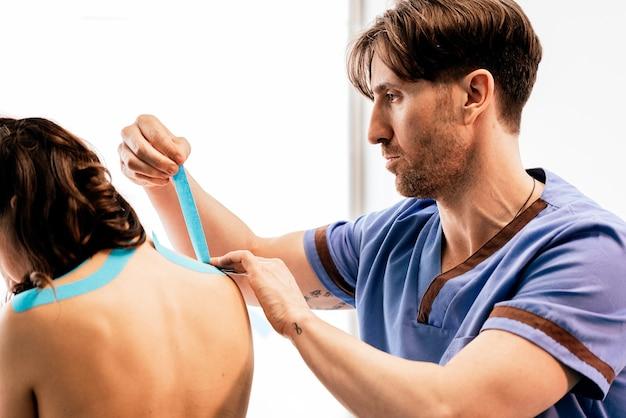 Fisioterapista che dà terapia della spalla a una donna in clinica. concetto di trattamento fisico